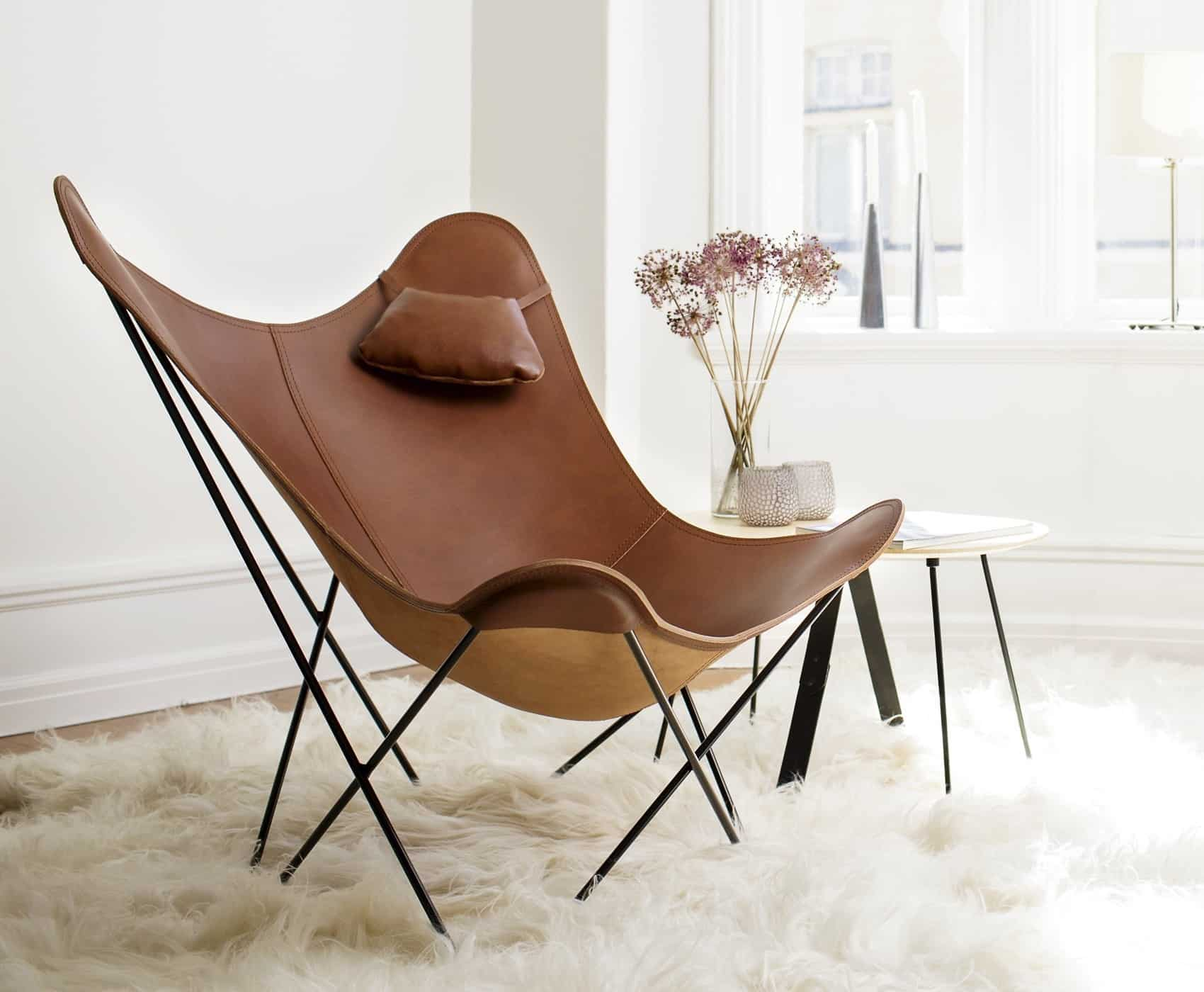A LEATHER BUTTERFLY CHAIR WITH A PILLOW
