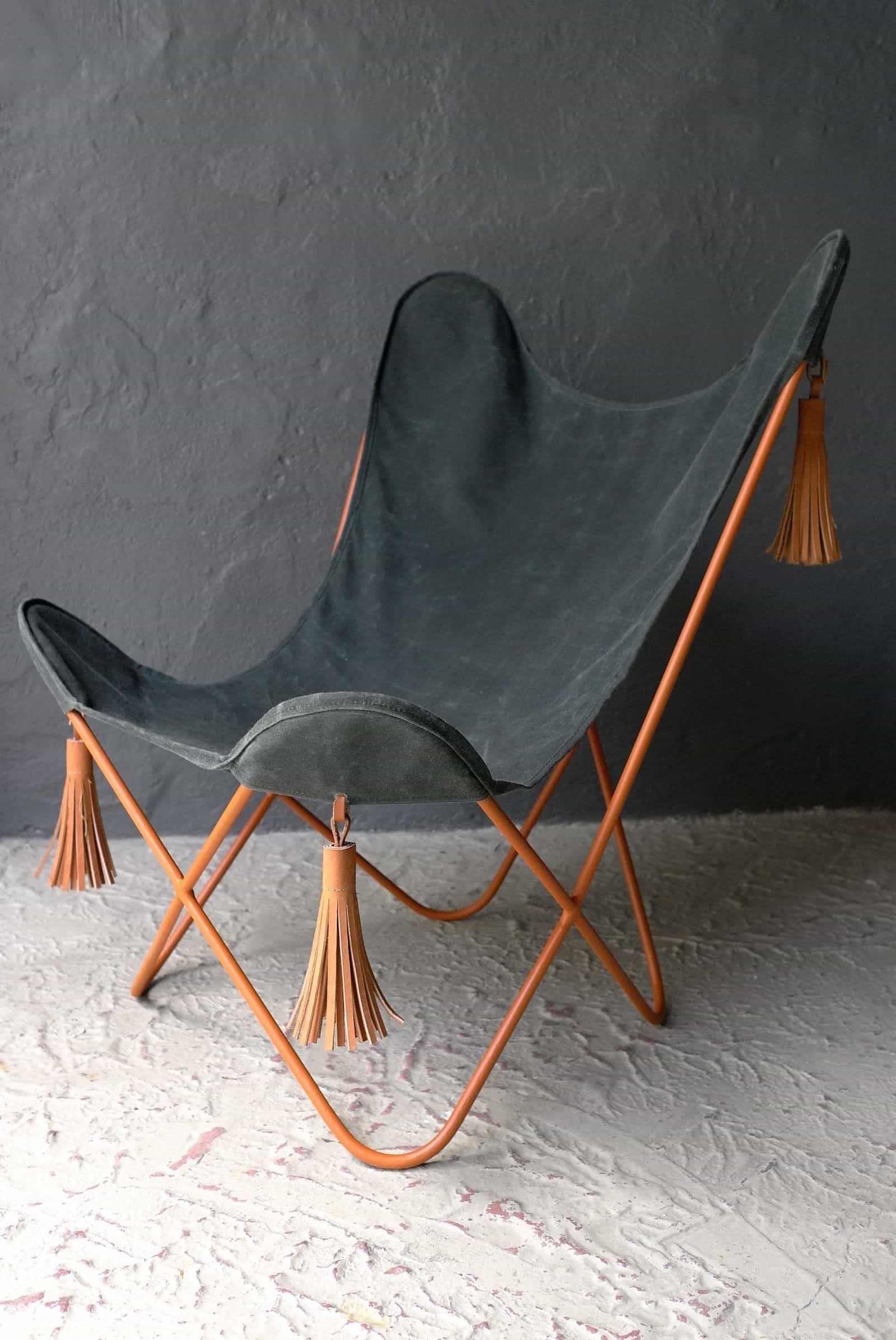 A WAXED CANVAS CHAIR WITH LEATHER TASSELS