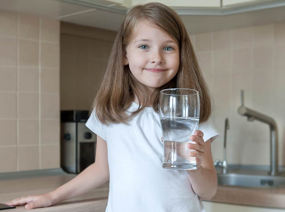 Portrait of a little caucasian baby girl holding a glass of tap clean water. Kitchen faucet.